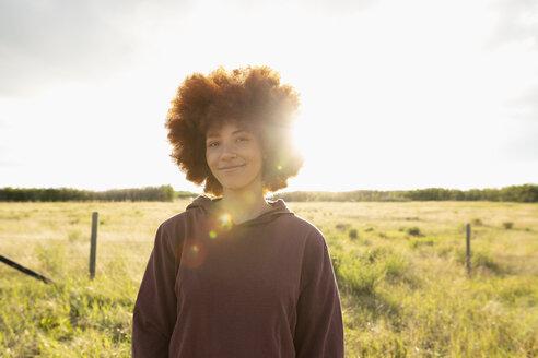 Portrait smiling, confident teenage girl in sunny rural field - HEROF12650