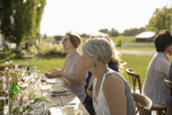 Smiling woman eating cake at garden party table - HEROF12656