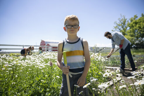 Portrait smiling confident boy gardening with family in sunny rural garden - HEROF12662