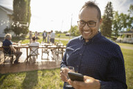Smiling man using smart phone at wedding reception in sunny rural garden - HEROF12668