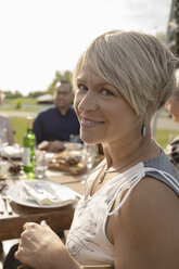 Portrait smiling woman enjoying wedding reception lunch at sunny patio table - HEROF12671