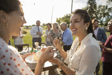 Smiling women eating cake, celebrating at sunny rural garden party - HEROF12677
