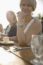 Smiling woman eating cake, celebrating at sunny garden party - HEROF12680