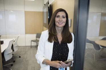 Portrait smiling, confident businesswoman using smart phone in office - HEROF12692