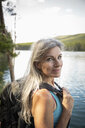 Portrait confident mature woman hiking at lakeside - HEROF12701