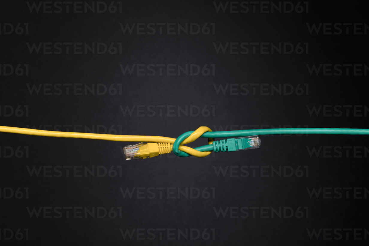 Contrasting green and yellow computer cables knotted on black background - HEROF12734 - Hero Images/Westend61