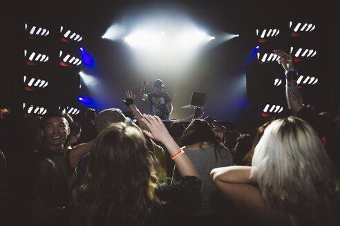 Crowd cheering for DJ performing on nightclub stage - HEROF12794