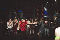 Enthusiastic young millennial couple dancing on nightclub dance floor - HEROF12821