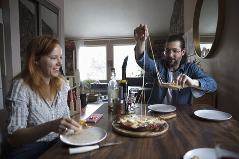 Couple enjoying homemade pizza at dining table - HEROF12869