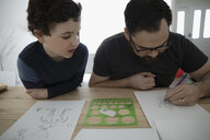 Curious son watching father drawing robot on paper - HEROF12896