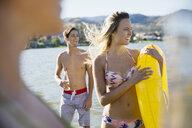 Smiling young woman in bikini holding inner tube at sunny summer lake - HEROF12914