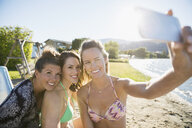 Smiling young woman friends taking selfie with camera phone on sunny summer lake beach - HEROF12917