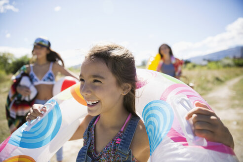 Smiling girl with inner tube in sunny summer field - HEROF12926