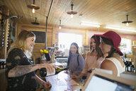 Vintner pouring wine for women friends wine tasting in winery tasting room - HEROF12977
