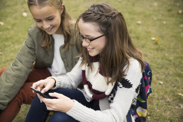 Tween girls texting with cell phone in park - HEROF13016
