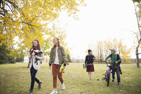 Tween girls and boy walking and talking in autumn park - HEROF13022