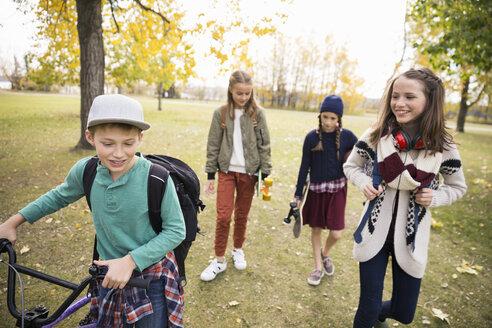 Tween boy and girls walking in autumn park - HEROF13025
