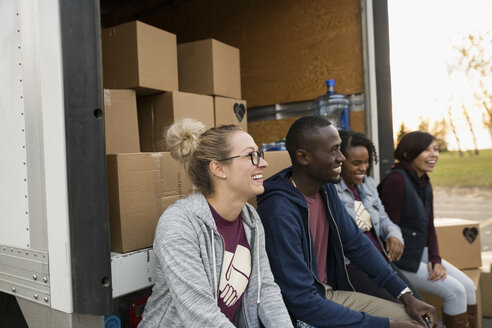 Smiling volunteers sitting at back of truck with cardboard boxes - HEROF13061
