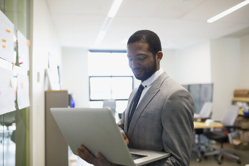 Businessman standing with laptop in office - HEROF13100