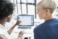 Businesswomen working at laptop in office - HEROF13118
