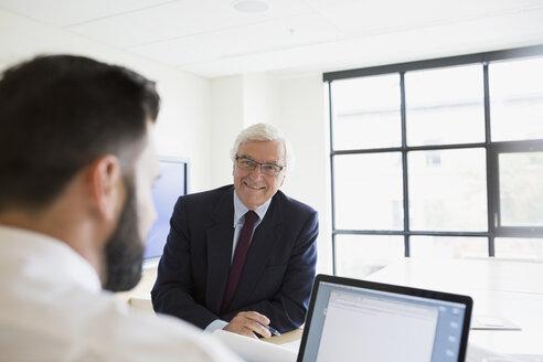 Businessmen using laptop in conference room - HEROF13127