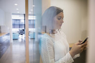 Businesswoman texting with cell phone in office - HEROF13145