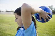 Close up middle school girl soccer player preparing soccer ball throw-in - HEROF13199