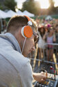 Close up DJ with headphones adjusting equipment on stage at summer music festival - HEROF13202