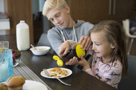 Brother helping sister pour syrup on pancakes at breakfast dining table - HEROF13208