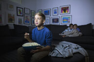 Brother and sisters eating popcorn watching movie in dark living room - HEROF13220