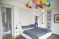 Boy jumping on bed below multicolor balloons - HEROF13229