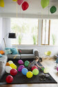Boy playing in living room with multicolor balloons - HEROF13235