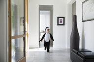Boy in killer whale costume running through foyer - HEROF13247