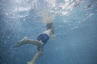 Boy swimming underwater in swimming pool - HEROF13259