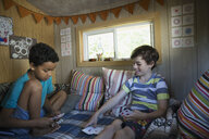 Boys playing cards in treehouse - HEROF13274
