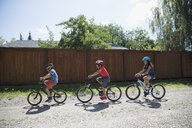 Boys and girl riding bicycles on sunny gravel road in a row - HEROF13280