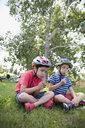 Boys wearing bike helmets blowing dandelions in grass at park - HEROF13283