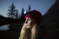 Blonde woman looking away wearing headlamp in the dark - HEROF13313