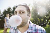 Close up portrait brunette man blowing bubble with bubble gum in sunny summer park - HEROF13319