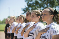 Middle school girl softball team pledging allegiance during national anthem - HEROF13325