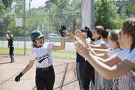 Middle school girl softball team high fiving teammate over fence - HEROF13328