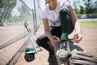 Middle school girl softball player tying shoe on bench - HEROF13340