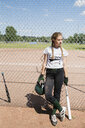 Middle school girl softball player with batting helmet and bat leaning on sunny fence - HEROF13343