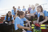 Middle school girl soccer team talking and preparing on bleachers - HEROF13346