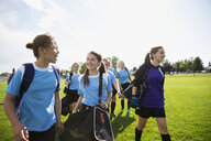 Middle school girl soccer team walking onto field - HEROF13349