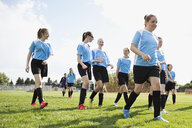 Middle school girl soccer team walking on sunny field - HEROF13352
