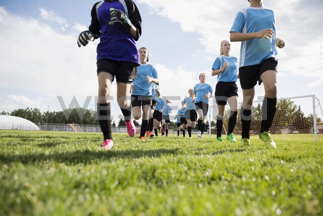 Middle school girl soccer team running onto sunny field - HEROF13355