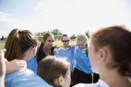 Middle school girl soccer team and coach huddling on field - HEROF13358