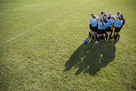 Middle school girl soccer team huddling with coach on sunny field - HEROF13364
