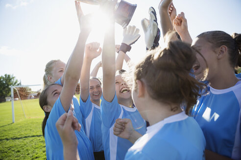 Middle school girl soccer team celebrating and cheering with trophy - HEROF13367